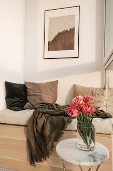 Gezellige comfortabele woonkamer met loggia-ligstoel, witte muur, mozaïektegel, marmeren tafel met boeket van roze pioenrozen, kussens, plaid en fotolijst