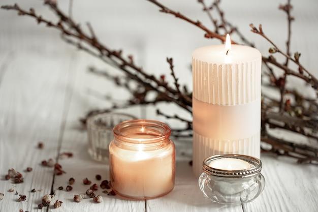 Gezellige compositie met brandende kaarsen en jonge boomtakken op een houten ondergrond in scandinavische stijl.
