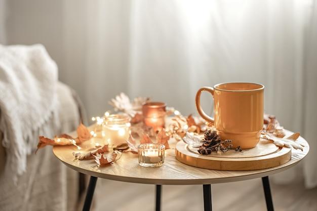 Gezellige compositie met een kopje, kaarsen en herfstbladeren in het interieur.