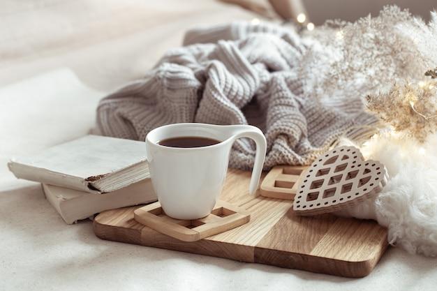Gezellige compositie met een kopje koffie op een schoteltje en interieurdetails.