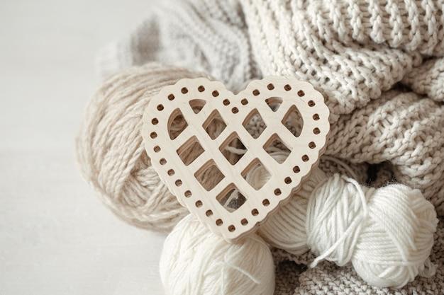 Gezellige compositie met gebreide items en een houten decoratief hart close-up.