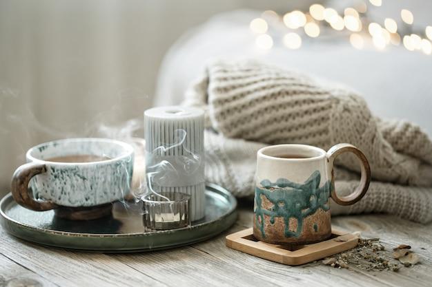 Gezellige compositie met keramische kopjes en kaarsen op een onscherpe achtergrond met bokeh.