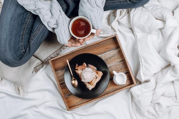 Gezellige flatlay van bed met houten dienblad met taart, ijs en zwarte thee en vrouwenhanden in grijze trui met beker