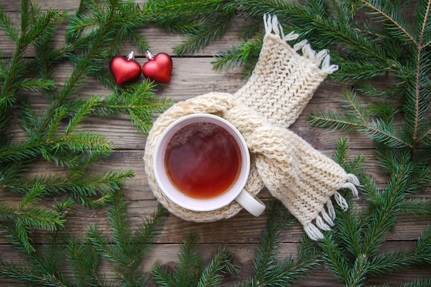 Gezellige foto met een mok thee in een sjaal, kerstboomtakken en rode harten op een rustieke houten achtergrond