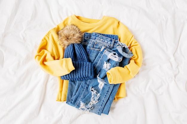 Gezellige gele trui, spijkerbroek en hoed op bed op wit laken. stijlvolle herfst- of winteroutfit voor dames. trendy kledingcollage. plat lag, bovenaanzicht.