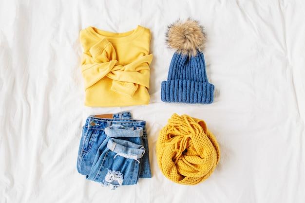 Gezellige gele trui, spijkerbroek, sjaal en muts op bed op wit laken. stijlvolle herfst- of winteroutfit voor dames. trendy kledingcollage. plat lag, bovenaanzicht.