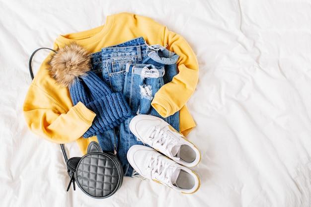 Gezellige gele trui, spijkerbroek, sneakers en hoed op bed op wit laken. stijlvolle herfst- of winteroutfit voor dames. trendy kledingcollage. plat lag, bovenaanzicht.
