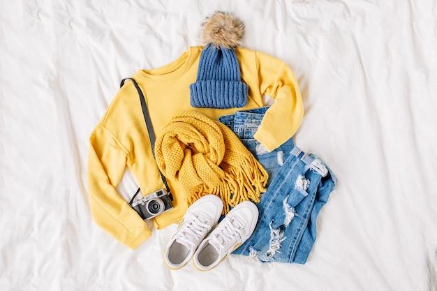 Gezellige gele trui, spijkerbroek, sneakers, sjaal liggend op bed op wit laken. stijlvolle herfst- of winteroutfit voor dames. trendy kledingcollage. plat lag, bovenaanzicht.