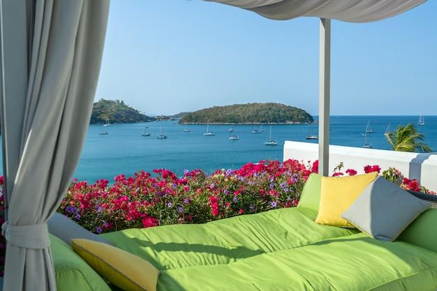 Gezellige groene bank met kussens op het terrein met uitzicht op de zee en de jachten