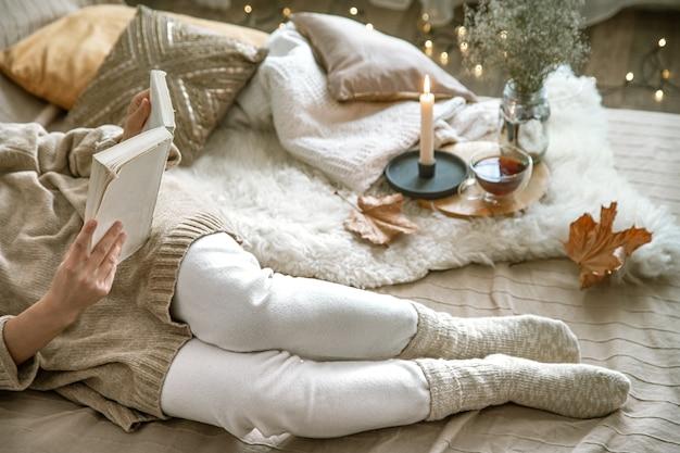 Gezellige herfst in huis, een vrouw met een boek in rust. gezellige manier van leven. lichaamsdelen in de compositie.