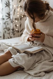 Gezellige herfst winterdag. vrouw hete thee drinken en boek lezen. comfortabele levensstijl