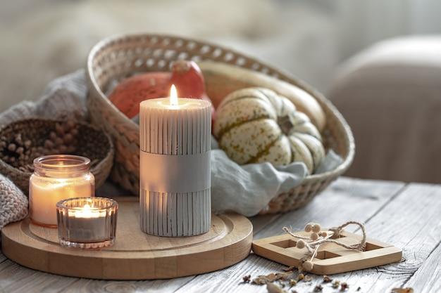 Gezellige herfstcompositie met brandende kaarsen en pompoenen op een onscherpe achtergrond.
