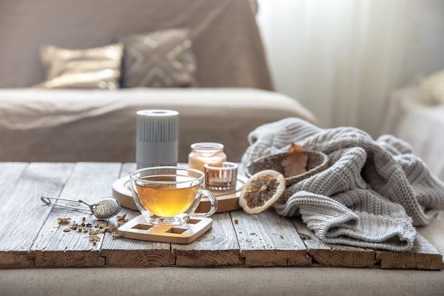 Gezellige herfsthuissamenstelling met een kopje thee, kaarsen en een gebreid element op een onscherpe achtergrond van het interieur van de kamer.