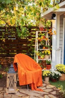 Gezellige herfstpatio met stoel, plaid, lantaarn, potchrysanten.