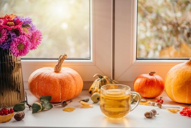 Gezellige herfstplattegrond met een kopje citroenthee, pompoenen en eikels