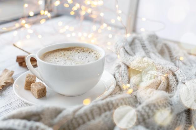 Gezellige herfstsamenstelling met kopje koffie, bruine suiker, gebreide sjaal, slinger