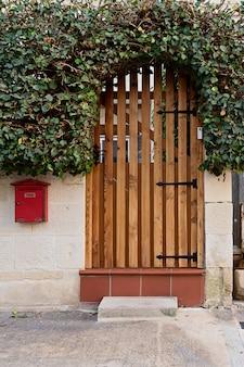 Gezellige houten voordeur met boog van struik bij de ingang van woonhuis