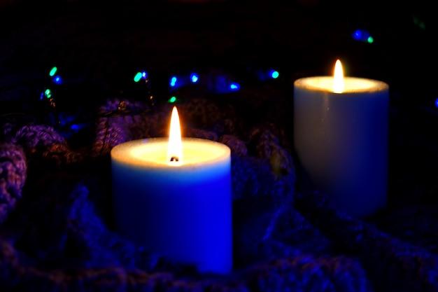 Gezellige huisachtergrond met een plaid en kaarsen bij nacht. brandende kaarsen en kerstverlichting.