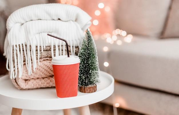 Gezellige huisdecoraties in het interieur met breiwerk, kerstboom en bakje cacao