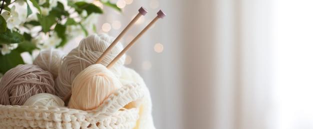 Gezellige huiselijke sfeer. vrouwelijke hobby breien. garen in warme kleuren. roze, perzik, beige, wit en groen. het begin van het proces van het breien van een damestrui.