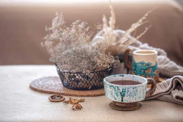 Gezellige huissamenstelling met een mooi keramiek kopje thee op tafel. decoratieve items in het interieur.