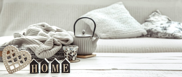Gezellige huissamenstelling met een theepot, gebreide items en scandinavische decordetails. concept van huiscomfort en moderne stijl.