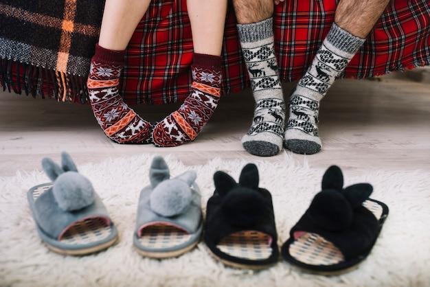 Gezellige huisschoenen op vloer dichtbij menselijke benen