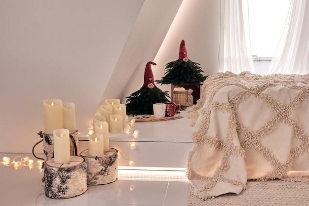 Gezellige kamer versierd met kaarsen en kerstboom met cadeautjes eronder