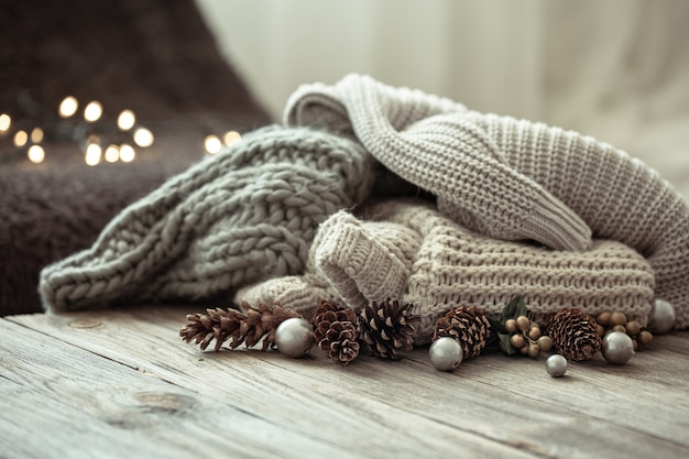 Gezellige kerstcompositie met een stapel gebreide truien en decoratieve dennenappels op een onscherpe achtergrond met bokeh.