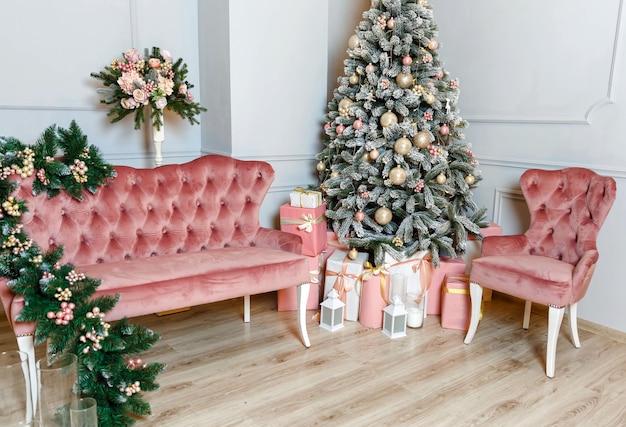 Gezellige lichte woonkamer met kerstboom, stoel en bank. prachtig kerstdecor in huis. geschenkdozen in de buurt van feestelijke dennen. gelukkig nieuwjaar en vrolijk kerstfeest. decoratie