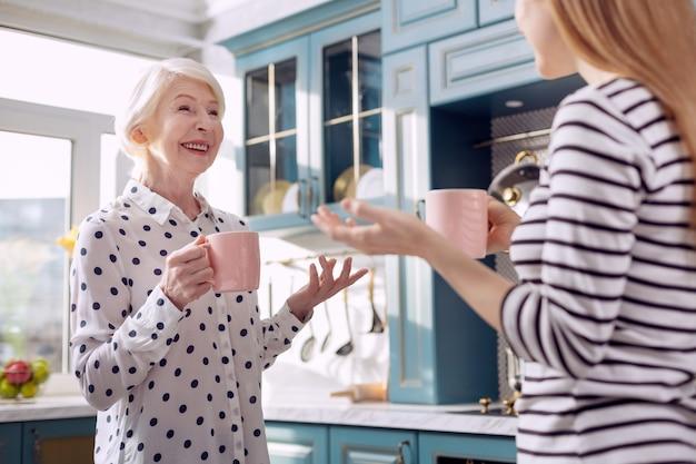 Gezellige ochtend. aangename oudere vrouw en haar volwassen dochter die met elkaar praten tijdens een kopje koffie en een stralende glimlach uitwisselen terwijl ze in de keuken staan