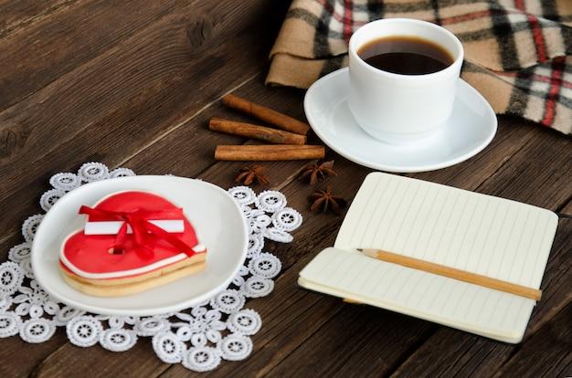 Gezellige rust. koffiemok, peperkoek in de vorm van een hart, notitieblok met potlood, kruiden