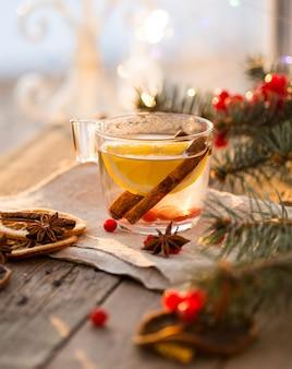 Gezellige scène voor open haard en kerstboom versierd speelgoed en kerstverlichting met een kopje thee op houten tafel, in landhuis, wintervakantie van kerstavond.