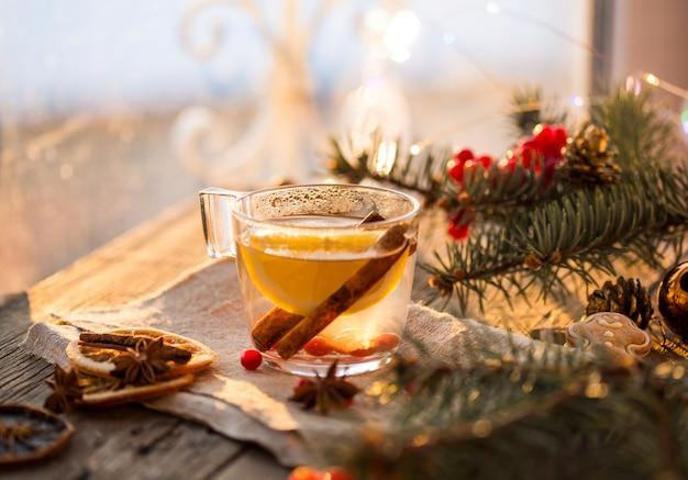 Gezellige scène voor open haard en kerstboom versierd speelgoed en kerstverlichting met kopjes thee op houten tafel, in landhuis, wintervakantie van kerstavond.