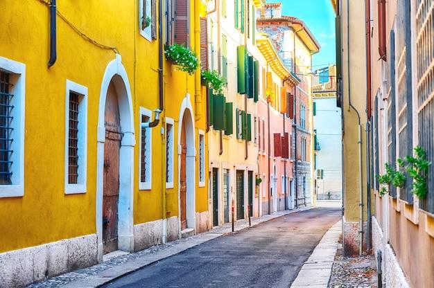 Gezellige smalle straatmening van de oude stad met kleurrijke huizen in verona, italië tijdens zonnige dag.