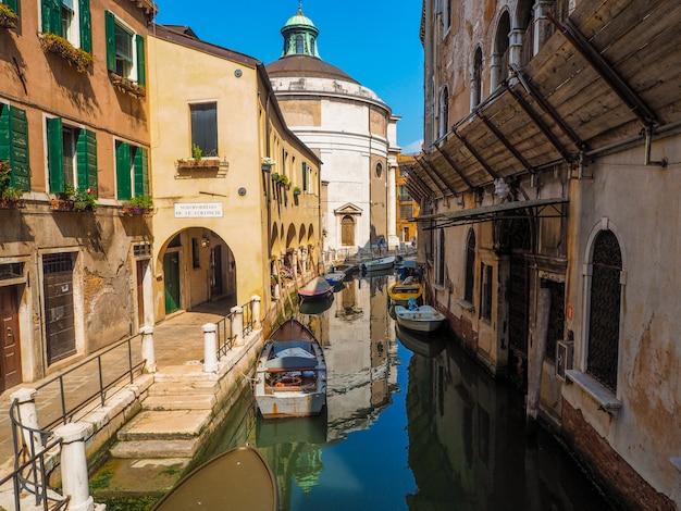 Gezellige straat in venetië met grachten en gondels, het toeristenseizoen in italië