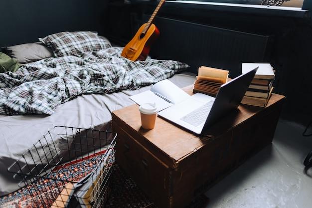 Gezellige thuiswerkplek met houten tafel, laptop en boeken bij het bed.