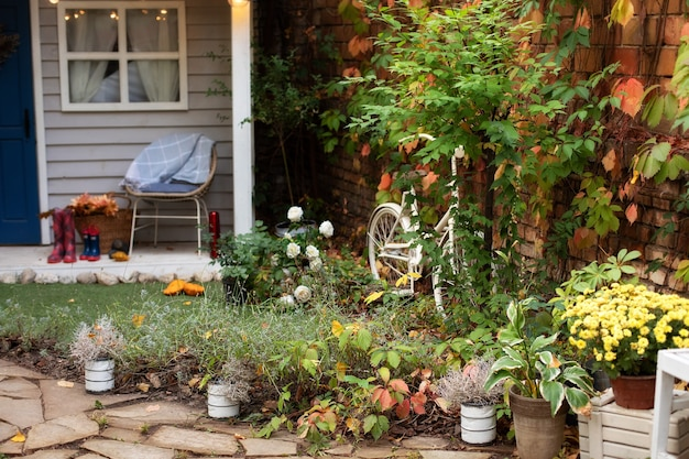 Gezellige tuinhoek van huis met kamerplanten in potten. huis terras in decor.
