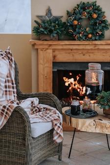 Gezellige versierde kerstveranda met een tafel met glühweinglazen en een stoel met een deken