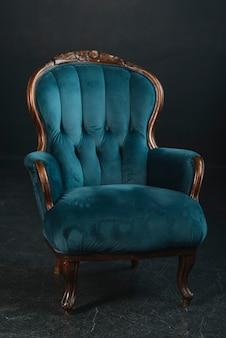 Gezellige vintage fauteuil tegen zwarte achtergrond