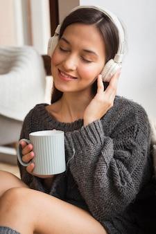Gezellige vrouw die met mok aan muziek luistert