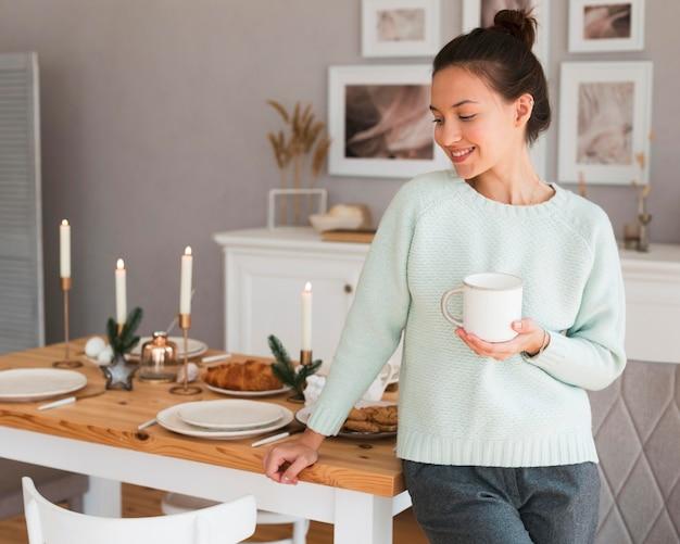 Gezellige vrouw leunend op de keukentafel en mok te houden