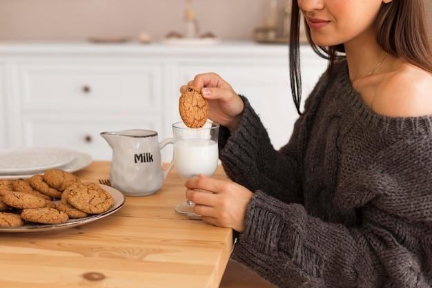 Gezellige vrouw met koekjes en melk