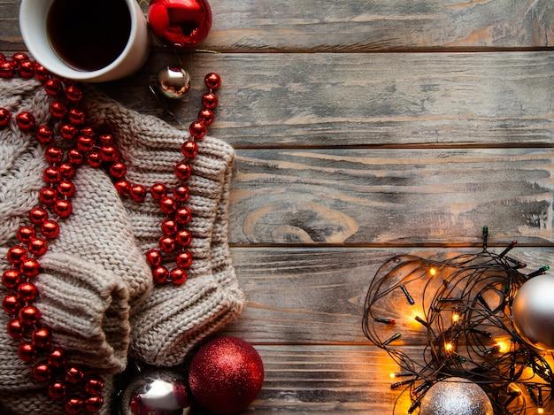 Gezellige warme vakantie decor op houten achtergrond. kerstsfeer en feestelijke stemming. fairy lights gebreide trui en rode kralen string met een kop warme koffie.