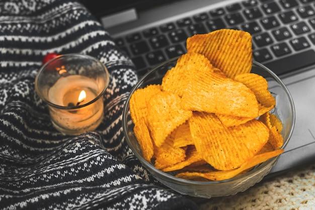 Gezellige winter en herfst warme nachten met film kijken en ongezond eten, chips in kom, gebreide trui close-up foto