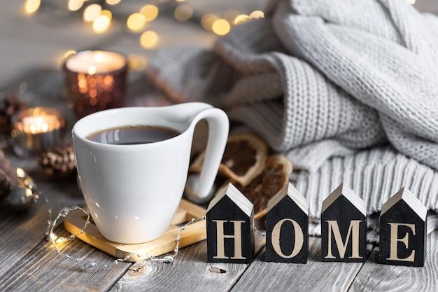 Gezellige wintercompositie met een kopje thee, het decoratieve woord huis, gebreide elementen en bokehlichten.