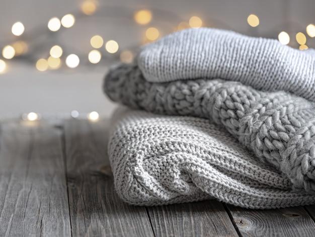 Gezellige wintercompositie met een stapel gebreide items op een onscherpe achtergrond met bokeh, kopieer ruimte.