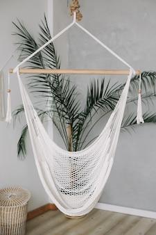 Gezellige witte hangmat in woonkamer relaxhoek met palmboom thuis