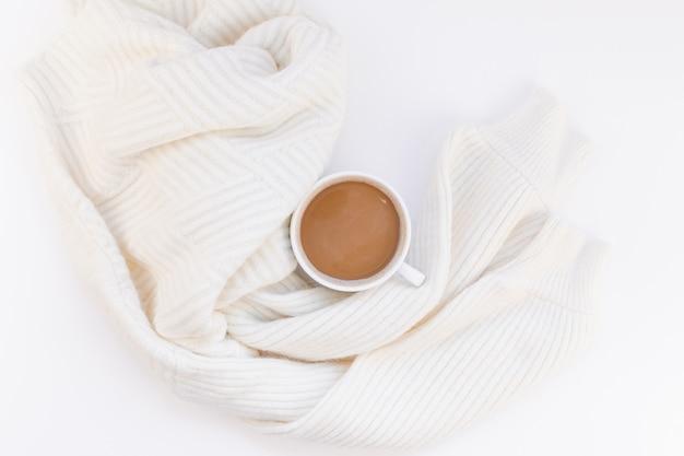 Gezellige witte warme trui en koffiekop herfststemming