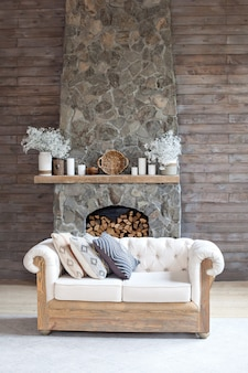Gezellige woonkamer met ecologisch decor. hout en aardconcept in binnenland van ruimte. scandinavisch interieur. hygge decoratie. gezellige stenen open haard met een witte bank en een houten muur. boho. rustiek interieur